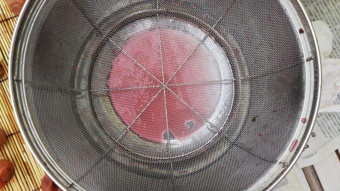 梅干をワンクッションおいたザルとボール(赤梅酢がたまっている)
